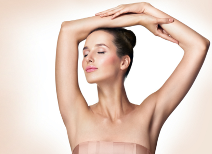 woman holding her arms up and showing clean underarms from laser hair removal