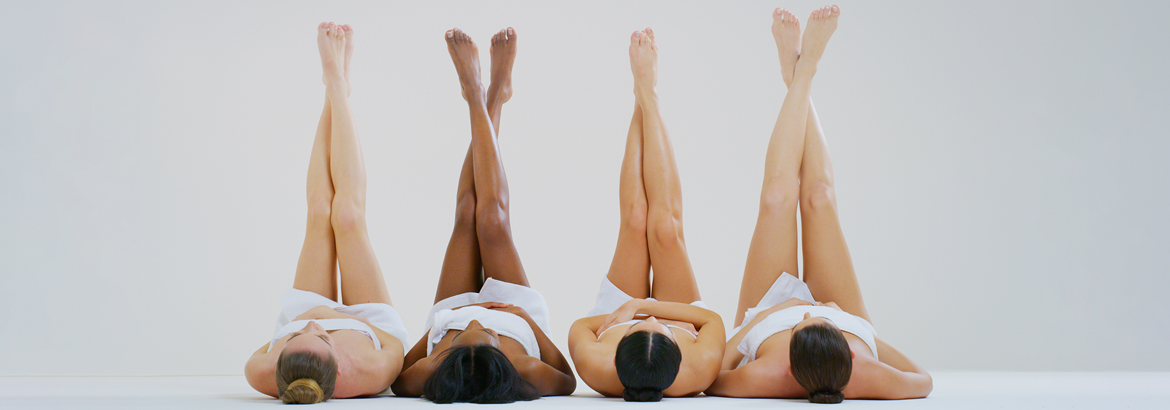 Four women with different skin tones with hairless soft and silky legs crossed