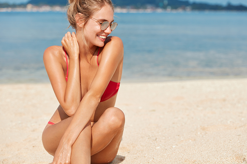 Tan woman on beach wearing sunglasses and bathing suit bathes in sun near ocean